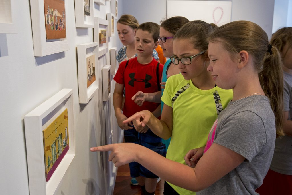Evelyn Montagna, center, 10, and Peyton Range, right, 10, look at art on display at the Fowler-Kellogg Art Center while touring the gallery with their 5th grade class from Panama Central School on Friday, June 17, 2016. The gallery opened a week early to give local students a chance to visit before their semester ends.